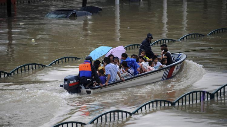 People are transported with a boat along a flooded street as heavy rainfall hits Lishui