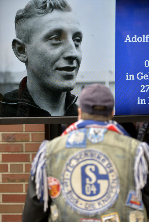 A Schalke fan looks at a picture of Adolf Urban, a storied player for  German soccer club FC Schalke 04 who was killed in Eastern Front fighting in World War II and  and who is being reburied in a cem