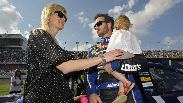 Jimmie Johnson, center, talks to his wife Chandra, left, as he holds their daughter Genevieve Marie, right, before the second of two NASCAR Gatorade Duel 150 qualifying auto races in Daytona Beach, Fla., Thursday, Feb. 23, 2012. (AP Photo/Rainier Ehrhardt)