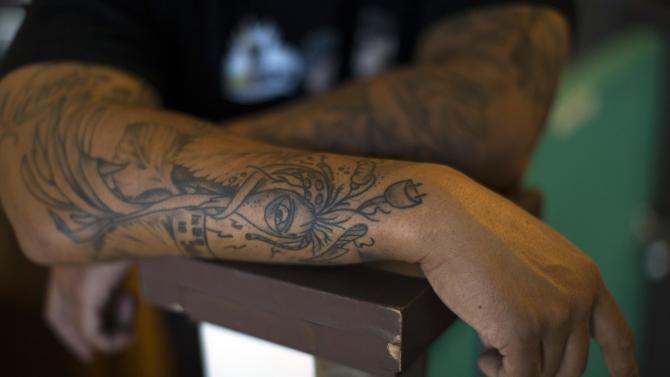 Tattoos are seen on the forearms of Kogi co-founder Roy Choi as he poses for a portrait at 3 Worlds Cafe in Los Angeles, California