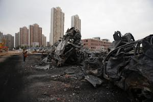 Damaged cars are seen at the site of the explosions …