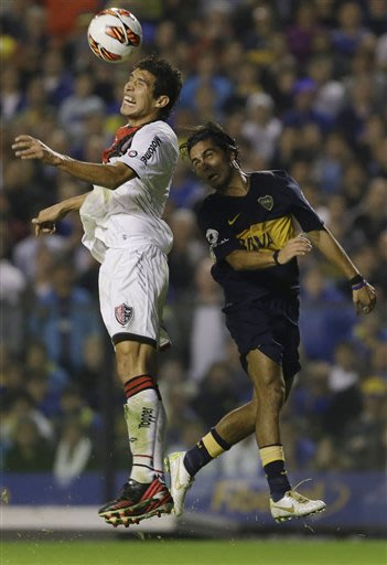 Argentina's Newell's Old Boys' Marcos Caceres, left, fights for the ball with Argentina's Boca Juniors' Walter Erviti during a Copa Libertadores quarterfinal soccer match in Buenos Aires, Argentina, T