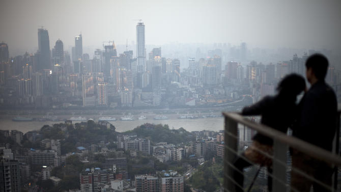 FILE - In this Tuesday, April 3, 2012 file photo, a couple observe the city skyline at a viewpoint in southwestern China's Chongqing city. The new leadership in the southwestern Chinese city beset by a murder scandal that took down its Communist Party boss says lessons must be learned from the embarrassing episode and efforts made to repair the city's image. (AP Photo/Alexander F. Yuan, File)