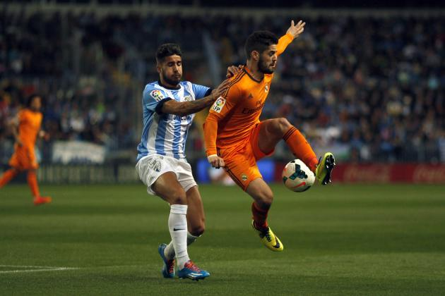 Real Madrid's Isco battles for the ball with Malaga's Samuel during Spanish First Division soccer match in Malaga