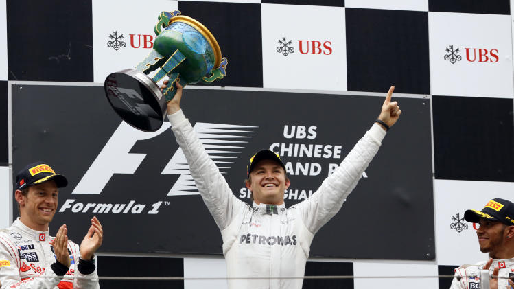 Mercedes Formula One driver Nico Rosberg of Germany, center, celebrates after winning the Chinese Grand Prix in Shanghai, Sunday, April 15, 2012. McLaren driver Jenson Button of Britain, who finished second, is at left, and his third placed team mate Lewis Hamilton of Britain is at right.   (AP Photo/Eugene Hoshiko)