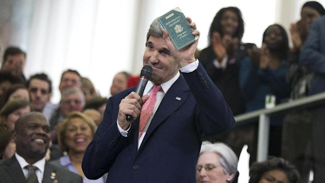 New Secretary of State John Kerry shows his first diplomatic passport he got when he was eleven years old when his father was in the foreign service, Monday, Feb. 4, 2013, during a ceremony welcoming him as the 68th secretary of state, at the State Department in Washington.   (AP Photo/Manuel Balce Ceneta)