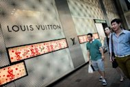 <p>Chinese mainland tourists walk past a luxury shop in Hong Kong. Giving gifts is crucial if you want to get ahead in Chinese politics or business, but sales of luxury goods have slipped recently amid an economic slowdown and uncertainty over Beijing's once-a-decade leadership transition.</p>