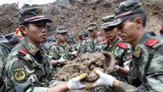 In this photo taken Thursday Oct. 4, 2012, Chinese paramilitary police move mud as they dug for children buried by a landslide in Yiliang county in southwest China's Yunnan province. All 18 elementary school students buried in the landslide were confirmed dead Friday, while one other person remained missing a day after the hillside collapsed and smothered part of a village in mountainous southwestern China. (AP Photo) CHINA OUT