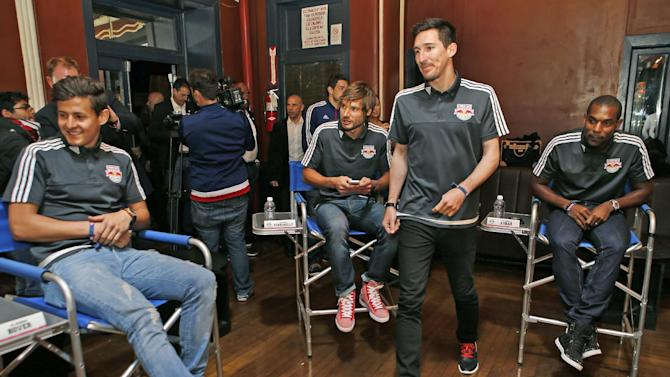 RETRANSMISSION TO CORRECT SPELLING FROM PERINELLE TO PERRIENELLE -lleNew York Red Bulls forward Sacha Kljestan, third from right, heads to his seat at the start of the Major League Soccer club's media day in New York, Tuesday, March 3, 2015.  From left, midfielder Ruben Bover, of Spain, defenders Damien Perrienelle, of France, and Ronald Zubar of Guadeloupe look on. (AP Photo/Kathy Willens)