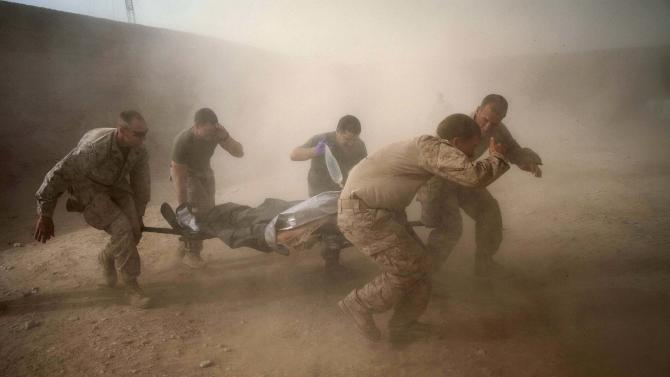 """In this picture taken Tuesday, May 10, 2011, United States Marines run through dust kicked up by a Blackhawk helicopter from Task Force Lift """"Dust Off"""", Charlie Company 1-214 Aviation Regiment as they rush a colleague wounded in an IED strike for evacuation near Sangin, in the volatile Helmand Province of southern Afghanistan. (AP Photo/Kevin Frayer)"""