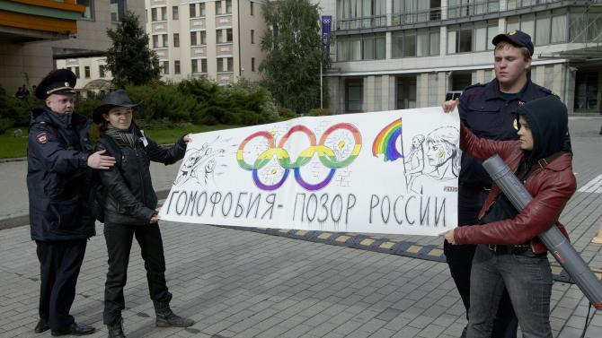 """FILE - In this Wednesday, Sept. 25, 2013 file photo, police officers detain two gay rights activists holding a poster reading """"Homophobia is Russia's Disgrace"""" during a protest outside the Sochi 2014 Winter Olympic Games organizing committee office, in downtown Moscow, Russia. Despite months of protests, Russia's law against """"gay propaganda"""" remains in place, and no major boycott of the Russian-hosted Winter Olympics seems likely. (AP Photo/Ivan Sekretarev, File)"""