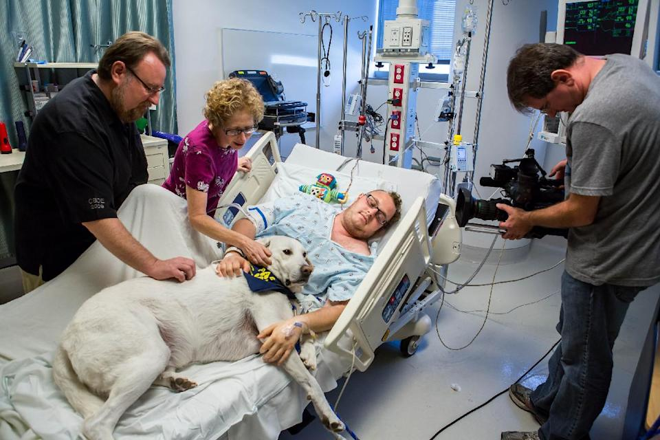 In this Nov. 7, 2012, photo released by Shelter Me shows Finn, a former shelter dog bringing comfort to patient Jacob Chodash, who had a brain tumor removed, and his parents at the Ronald Reagan UCLA Medical Center in Los Angeles. (AP Photo/Shelter Me, Martin Ehleben)