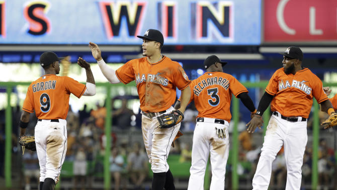 Miami Marlins second baseman Dee Gordon (9), right fielder Giancarlo Stanton, second from left, shortstop Adeiny Hechavarria (3) and center fielder Marcell Ozuna, right, celebrate after defeating the Washington Nationals 6-2 in a baseball game, Sunday, April 26, 2015, in Miami. (AP Photo/Lynne Sladky)