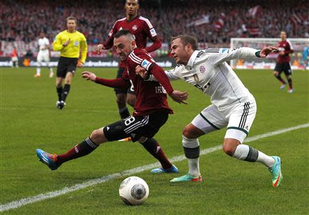 Bayern Munich's Goetze is tackled by Drmic of Nuremberg during German Bundesliga soccer match in Nuremberg