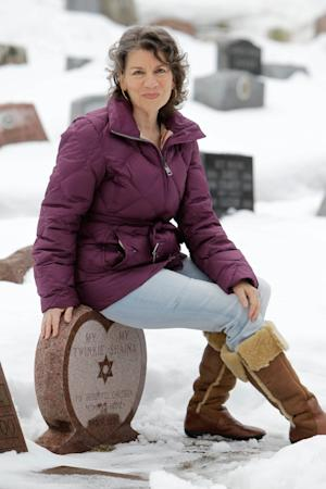 FILE - In this Jan. 19, 2011 file photo, Rhona Levy poses for a picture at the grave site where she has buried some of her pets and plans to have her own remains buried at the Hartsdale Pet Cemetery in Hartsdale, N.Y. The New York State Cemetery Board has proposed regulations that will once again permit pet owners to have their ashes interred with their beloved animals in pet cemeteries. (AP Photo/Seth Wenig, File)