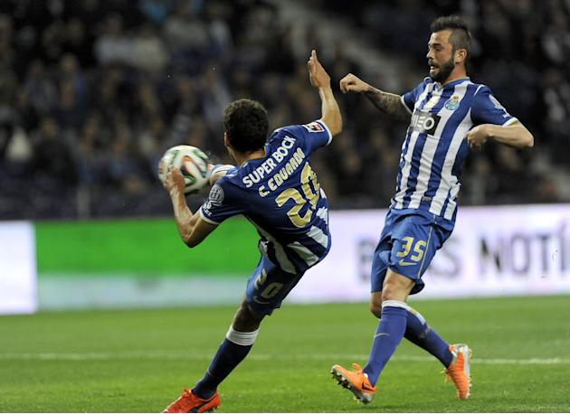 FC Porto's Carlos Eduardo, from Brazil, shoots to score his team second goal against Arouca, with teammate Steven Defour from Belgium at right, in a Portuguese League soccer match at the Dragao st