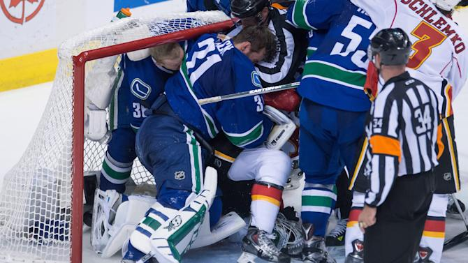 Vancouver Canucks goalie Eddie Lack (31), of Sweden, punches Calgary Flames' Brandon Bollig (25) after Bollig fell on him during the second period of Game 2 of an NHL hockey first-round playoff series, Friday, April 17, 2015, in Vancouver, British Columbia. (Jonathan Hayward/The Canadian Press via AP)