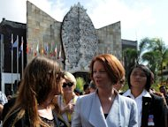 Australian Prime Minister Julia Gillard (C) meets an Australian citizen during a visit to the 2002 Bali bombings memorial monument in the Kuta tourist area near Denpasar, on the Indonesian resort island of Bali, on October 13. Gillard paid her respects to the 202 people who perished a decade ago in the bombings