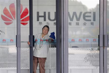 File photo shows a cleaner wiping the glass door of a Huawei office in Wuhan