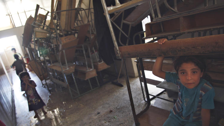 A Syrian girl sits on a desk at the school where she and her family  took refuge from the fighting, in the town of Kafr Hamra, ten kilometers.(six miles) north of the center of  Aleppo city, Syria, Tuesday, Aug. 7, 2012. (AP Photo/ Khalil Hamra)