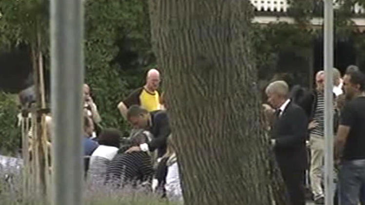 In this image from TV, Norway's Prime Minister Jens Stoltenberg, centre, bends down to comfort an unidentified man outside a hotel where survivors are being reunited with family members in Sundvollen, Norway, Saturday, July 23, 2011.  A Norwegian dressed as a police officer gunned down at least 84 people at an island youth retreat before being arrested, police said Saturday. Investigators are still searching the surrounding waters, where people tried to flee from the attack, which followed an explosion in nearby Oslo city centre. (AP Photo) TV OUT