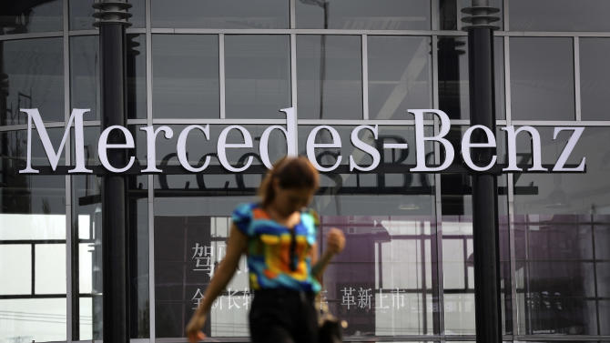 A woman walks past the Mercedes-Benz's dealer showroom in Beijing, China Monday, Aug. 18, 2014. China's government said Monday it has concluded Mercedes-Benz violated anti-monopoly law and charged excessive prices for parts, adding to a growing number of global automakers snared in an investigation of the industry. (AP Photo/Andy Wong)