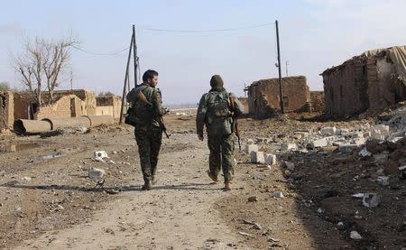 Members of the Kurdish People's Protection Units walk past an area damaged by what activists said was a car blown up by a suicide bomber loyal to the Islamic State in Al-Hras