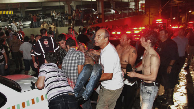 A victim of a nightclub fire is carried in Santa Maria city, Rio Grande do Sul state, Brazil, early Sunday, Jan. 27, 2013.  According to police, more than 200 died in the fire and at least 200 people were also injured. Officials say the fire broke out at the Kiss club while a band was performing. (AP Photo/Agencia RBS, Deivid Dutra)