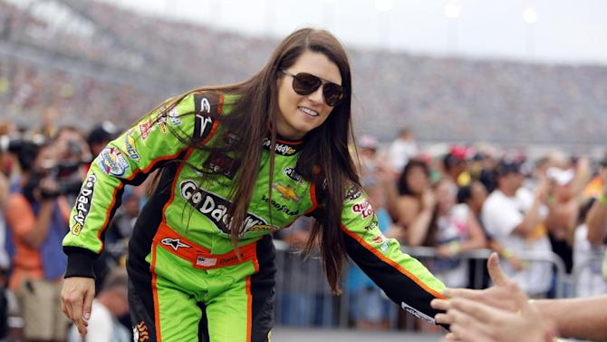FILE - In this May 11, 2013 file photo, driver Danica Patrick high fives fans during driver introductions before the start of the NASCAR Sprint Cup series auto race at Darlington Raceway, in Darlington, S.C. New country music fan Patrick will co-host the American Country Awards Tuesday, Dec. 10, 2013, on FOX with Trace Adkins. (AP Photo/Mic Smith, File)