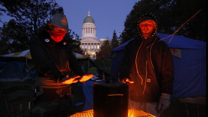 Occupy Maine protesters warm their hands while brewing coffee on a fire pit at their encampment across from the State House in Augusta, Maine, early Friday morning, Oct. 28, 2011. About 30 protesters camped out in near-freezing temperatures as they continue their protest against Wall Street. (AP Photo/Robert F. Bukaty)