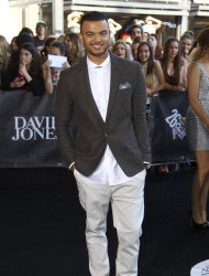 Guy Sebastian smiles at photographers upon arrival for the Australian music industry Aria Awards in Sydney, Thursday, Nov. 29, 2012. (AP Photo/Rick Rycroft)