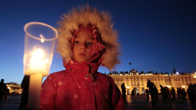 A child lights a candle during a ceremony to mark Earth Hour at Palace Square  in St.Petersburg, Russia, Saturday, March 31, 2012. Earth Hour takes place worldwide at 8.30 p.m. local times and is a global call to turn off lights for 60 minutes in a bid to highlight the global climate change. (AP Photo/Dmitry Lovetsky)