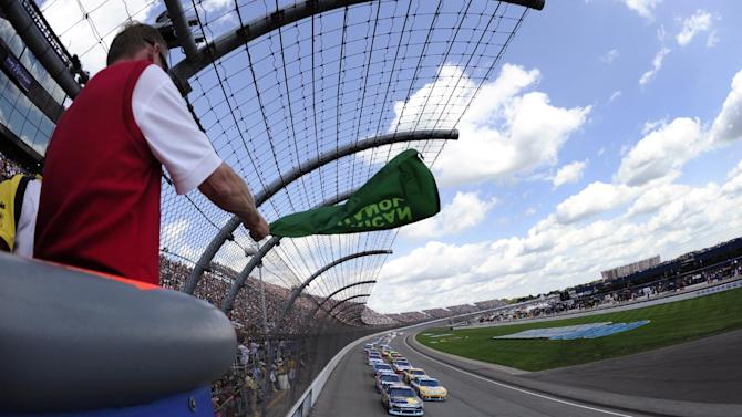 Alan Mulally, president and CEO of Ford Motor Co., waves the green flag for the start of the NASCAR Sprint Cup Series auto race at Michigan International Speedway in Brooklyn, Mich., Sunday, Aug. 21, 2011. (AP Photo/Jared C. Tilton, Pool)