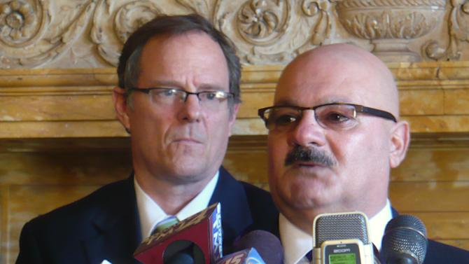 Elvin Daniel, right, whose sister Zina was killed by her husband last October at a Brookfield spa, said the tragedy could have been avoided if the law required background checks for private transactions of guns during a news conference with law enforcement officials and some Democratic lawmakers, including Rep. Jon Richards, left, Thursday, March 21, in Madison, Wis.  Democrats have a new proposal that would make it illegal to purchase or transfer guns without running background checks. (AP Photo/Kevin Wang)