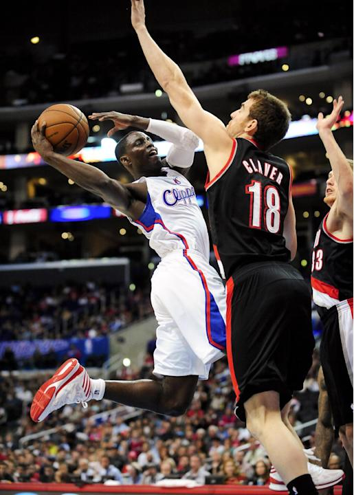 Los Angeles Clippers guard Darren Collison, left, drives on Portland Trail Blazers forward Victor Claver (18), of Spain, as he goes to the basket in the second half of a pre-season NBA basketball game