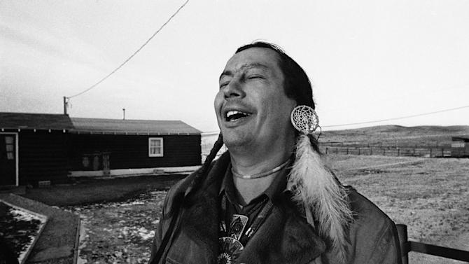"""FILE - In a Feb. 4, 1974 file photo, American Indian Movement (AIM) leader Russell Means, who is challenging incumbent Oglala Sioux Tribal President Richard Wilson in Thursday's election on the Pine Ridge Indian Reservation, laughs at news report which quoted Wilson as saying he will give AIM 10 days to get off the reservation after he is reelected """"or else"""", in Pine Ridge, S.D. Means, a former American Indian Movement activist who helped lead the 1973 uprising at Wounded Knee, reveled in stirring up attention and appeared in several Hollywood films, died early Monday, Oct. 22, 2012 at his ranch in in Porcupine, S.D., Oglala Sioux Tribe spokeswoman Donna Solomon said. He was 72. (AP Photo/Jim Mone, File)"""