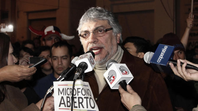 "FILE - In this June 24, 2012 file photo, Paraguay's former President Fernando Lugo talks through the ""open microphone"" of the Public Television, surrounded by reporters and followers in downtown Asuncion, Paraguay. Lugo spoke in a pre-dawn special televised ""open microphone"" program hosted by the state-funded Public Television channel that was created by his government, to denounce his ouster as a ""parliamentary coup"". A shootout that killed 11 farmworkers and 6 police officers prompted Lugo's opponents shortly thereafter to vote the sandal-wearing leftist out of office for ""mismanaging"" the property dispute. Paraguayans' hopes that Lugo would make good on his promises of land reform died.  (AP Photo, File)"