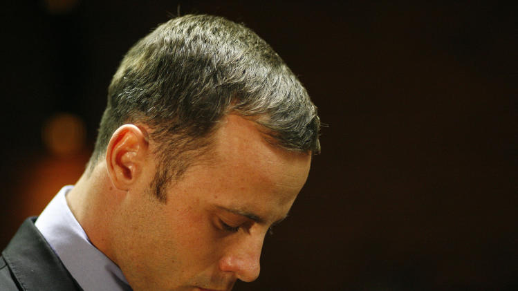 FILE - In this Feb. 21, 2013 file photo, Olympic athlete Oscar Pistorius stands during his bail hearing at the magistrate court in Pretoria, South Africa.Pistorius has been spending time with people who were close to the girlfriend he shot and killed on Valentine's Day, the Olympian's family said Thursday, April 11, 2013 in an indication that Pistorius is becoming more active while awaiting trial on a murder charge. (AP Photo/Themba Hadebe, File)