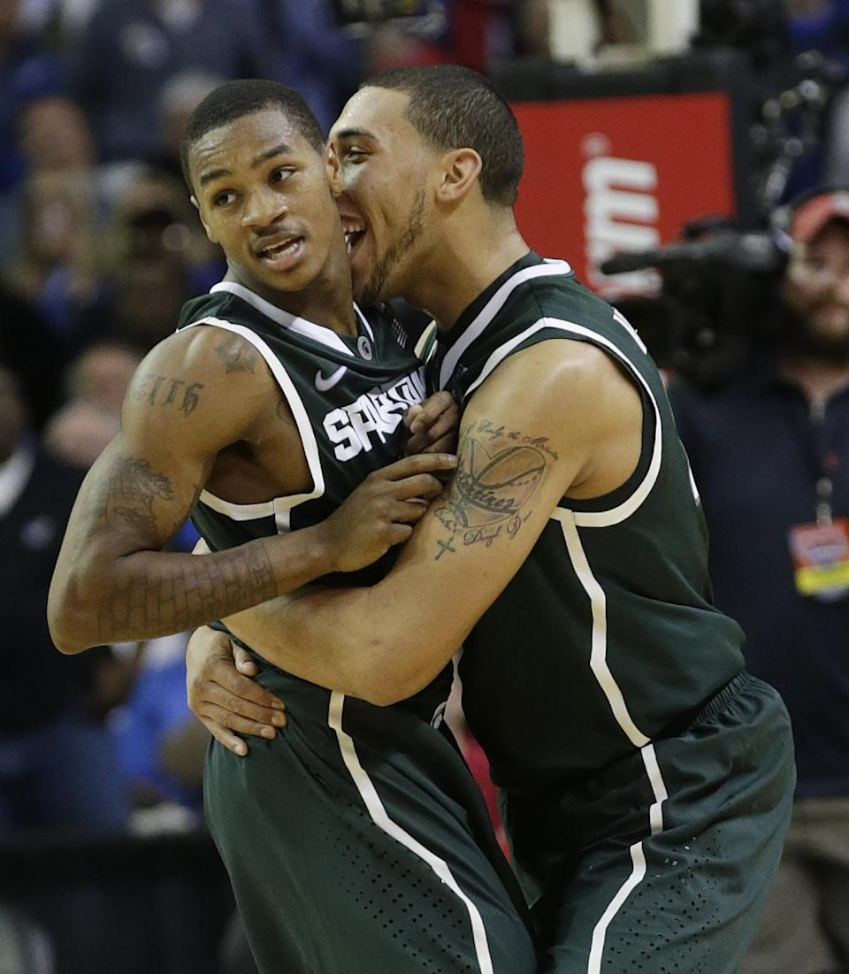 Michigan State guard Keith Appling, left, react with teammate Denzel Valentine, right, during the second half of an NCAA college basketball game at the Georgia Dome in Atlanta Tuesday, Nov. 13, 2012. Michigan State beat Kansas 67-64. (AP Photo/Dave Martin)