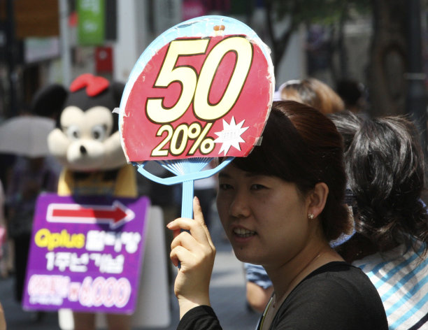 A sales clerk holds up a discount sale sign as she waits for customers at a cosmetic store in Seoul, South Korea, Thursday, July 26, 2102. South Korea's economic growth fell to a two-year low in the second quarter as exports and capital expenditures shrank due to a slowdown in its largest trading partner, China, and debt-crippled Europe.(AP Photo/Ahn Young-joon)