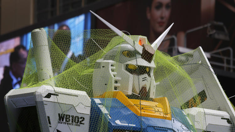 A 1/3 scale model of the giant robot Gundam is fixed by safely nets and wires during an exhibition under typhoon in Hong Kong Wednesday, Aug. 14, 2013. Typhoon Utor lashed Hong Kong with wind and rain, closing down the bustling Asian financial center Wednesday before sweeping toward mainland China. (AP Photo/Vincent Yu)