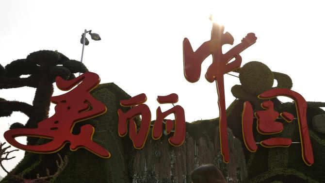 "A woman wearing a mask walks past a decoration for the China National Tourism Campaign with a slogan ""Beautiful China"" on display along the Chang'an Avenue in Beijing Monday, Oct. 21, 2013. As northern China entered its high-smog season, one city's visibility was less than half a football field Monday and Patti Austin's manager said the American jazz singer had been forced to cancel a concert in the capital, Beijing, on Friday evening after suffering a severe asthma attack likely linked to air pollution. (AP Photo/Andy Wong)"