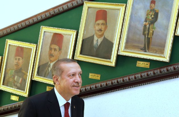Turkish Prime Minister Recep Tayyip Erdogan looks at paintings showing Egyptain defence ministers of the early part of the last century upon his arrival at the defence ministry in Cairo, Egypt, Tuesda