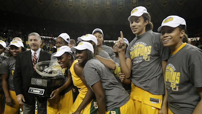 The Baylor basketball team poses with the Big 12 Conference Title trophy and conference commissioner Bob Bowlsby, left, in black jacket, following an NCAA college basketball game against Texas Saturday, Feb. 23, 2013, in Waco, Texas. Top-ranked Baylor celebrated a Big 12 title already in hand with dozens of former players in the stands for a 67-47 victory against Texas on Saturday. (AP Photo/Tony Gutierrez)