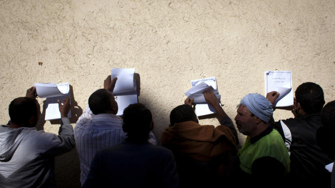 Egyptian voters check voter lists outside a polling station during the second round of a referendum on a disputed constitution drafted by Islamist supporters of president Mohammed Morsi, in Giza, Egypt, Saturday, Dec. 22, 2012. (AP Photo/Nasser Nasser)