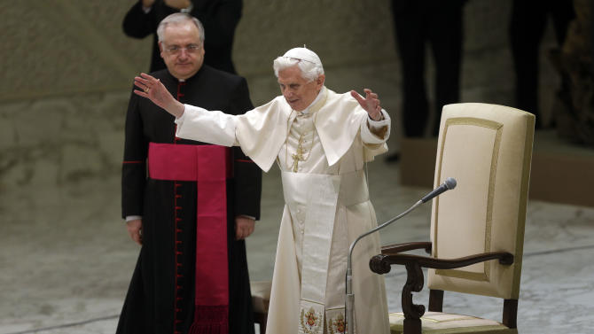 Pope Benedict XVI, right, acknowledges the crowd during his weekly general audience in Hall Paul VI, at the Vatican, Wednesday, Dec. 19, 2012. (AP Photo/Alessandra Tarantino)