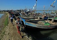 Muslim Rohingya men walk past fishing boats near the temporory relief camp at Bawdupha on the outskirts of Sittwe, capital of Myanmar's western Rakhine state. Police shot and killed one ethnic Rakhine during renewed clashes on Tuesday, a government official told AFP, declining to be named. The death brings the toll from the latest unrest to 89