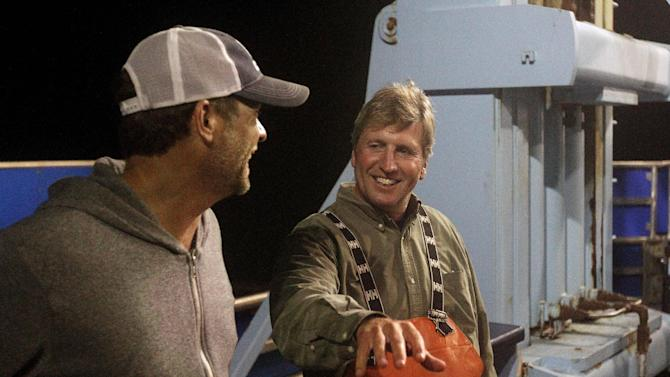 In this Sept. 13, 2012, photo, Massachusetts shark expert Greg Skomal, right, and expedition leader Chris Fischer discuss their success after tagging their first Atlantic great white shark on the research vessel Ocearch off the coast of Chatham, Mass. Skomal named the nearly 15-foot, 2,292-pound female shark Genie for famed shark researcher Eugenie Clark. The Ocearch team baits the fish and leads them onto a lift, tagging and taking blood, tissue and semen samples up close from the world's most feared predator. The real-time satellite tag tracks the shark each time its dorsal fin breaks the surface, plotting its location on a map. (AP Photo/Stephan Savoia)