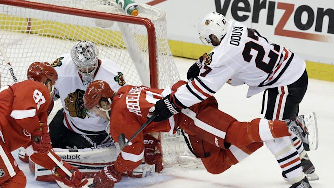 Chicago Blackhawks defenseman Johnny Oduya (27), of Sweden, checks Detroit Red Wings left wing Justin Abdelkader (8) in front of goalie Corey Crawford (50) during the second period of an NHL hockey Stanley Cup playoffs Western Conference semifinal game in Detroit, Monday, May 20, 2013. (AP Photo/Paul Sancya)