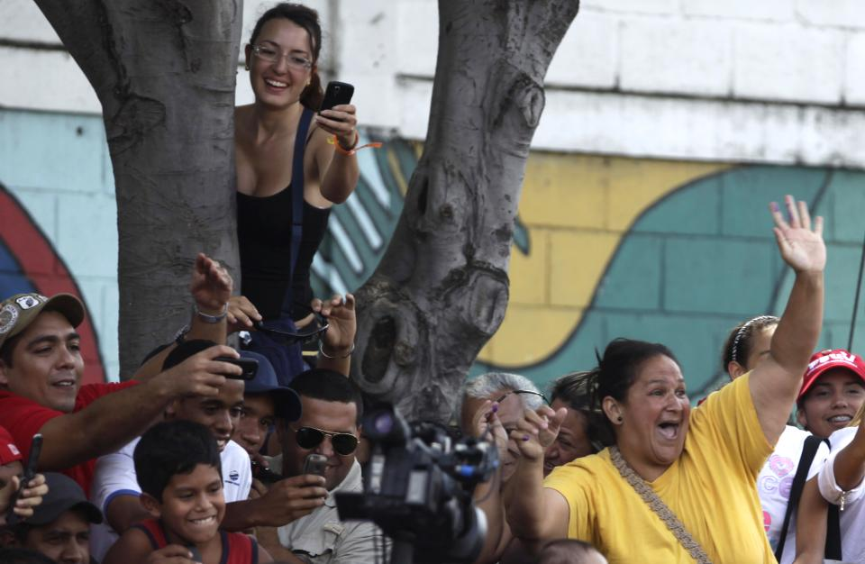 Supporters of President Hugo Chavez react as Chavez arrives to a polling station during the presidential election in Caracas, Venezuela, Sunday, Oct. 7, 2012.  Chavez is running for re-election against opposition candidate Henrique Capriles. (AP Photo/Enric Marti)